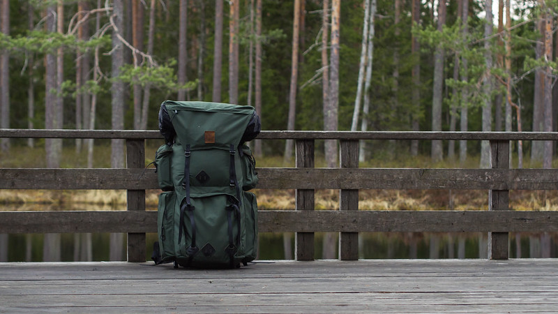 a hiking backpack on a deck outdoors with trees in the background