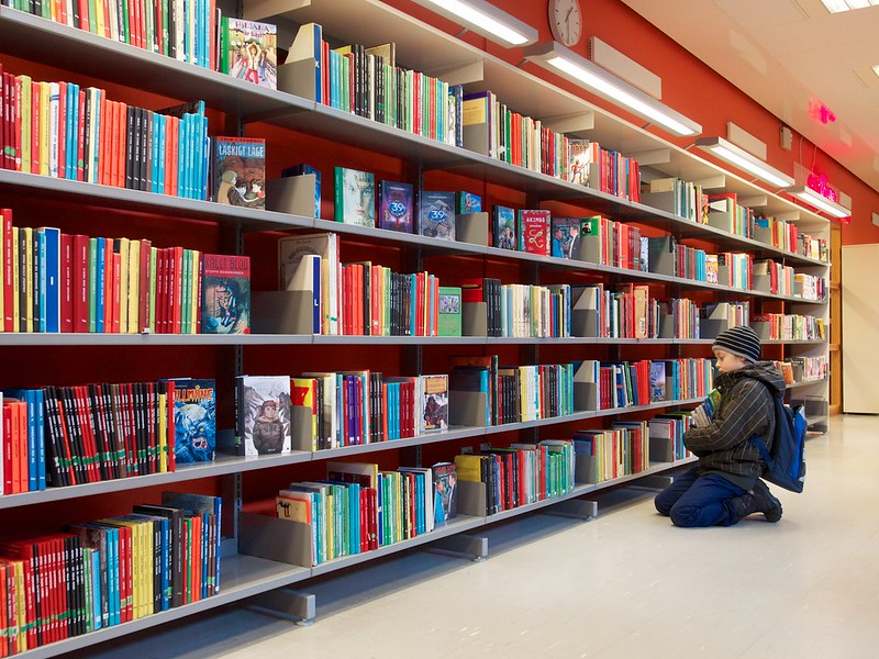 a student getting books from a library shelf